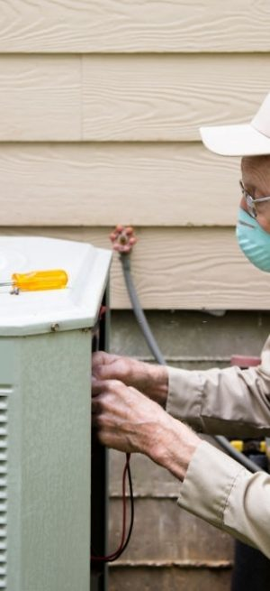 Mature Adult air conditioner Technician/Electrician  services outdoor unit.  He wears a protective face mask. He wears a Khaki uniform and hat.  His tool kit is sitting on top of the outside AC unit.